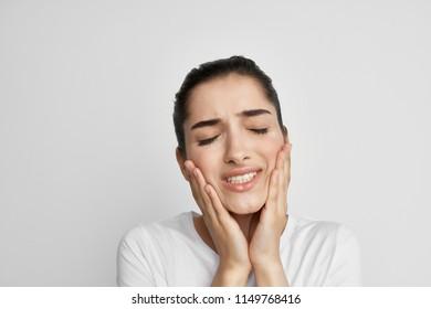A woman in a white t-shirt aching teeth dentistry.
