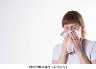 woman in white t-shirt sneezes, covering her nose with a napkin