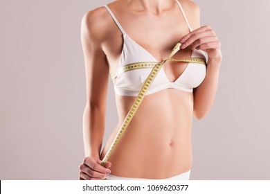 Woman in white underwear measuring breast volume, perfect female body