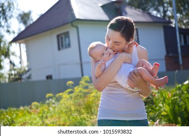 Woman in white vest holding baby on arms against a house