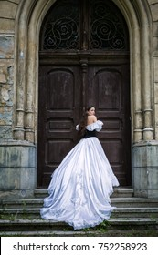 Woman in white Victorian dress with old door