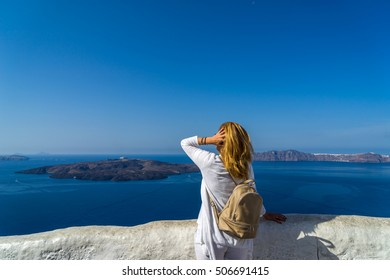 Woman in white visiting the of the famous white island of Santorini in Greece