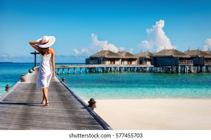 Woman in white walking over a wooden jetty in the Maldives