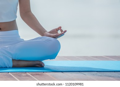 Woman in white yoga suit sitting meditation in the morning, Meditation has great calming effects and to recharge more energy throughout the day.
