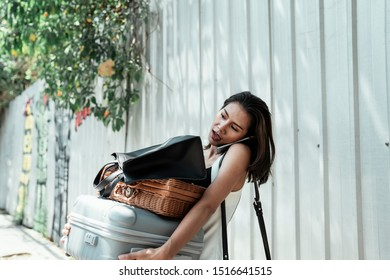 Woman of whitedress carrying bags and talking on the phone.