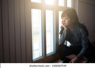 The woman who was absent-minded and sorrowful, sat looking out the window.
