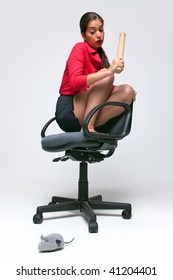 Woman who doesn't like mice crouched on an office chair holding a rolling pin as a clockwork mouse runs around on the floor.