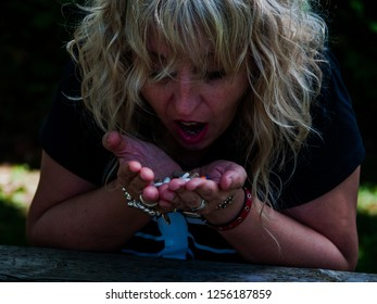 A woman who is going to ingest a large number of pills in her hand, of different sizes and colors