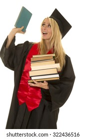 A woman who is graduating holding up a book with a smile on her face.
