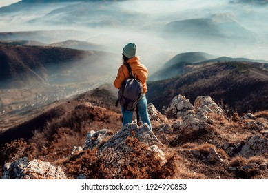 a woman who hikers enjoys a break look at the top of the mountain