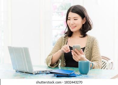 明るい部屋でパソコンとスマートフォンを操作する女性