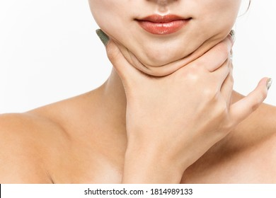 A woman who pinches the fat on her jaw.