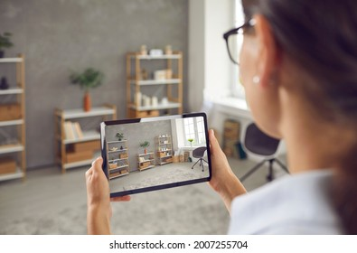 Woman who plans on selling her studio apartment taking photo of stylish decor in custom design living room interior on her smart tablet. Young blogger or house seller giving video tour around her home