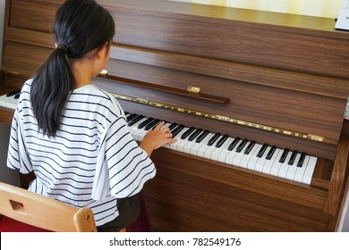 The woman who plays an upright piano.