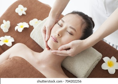 A woman who receives face massage and an esthetician who performs treatment.
