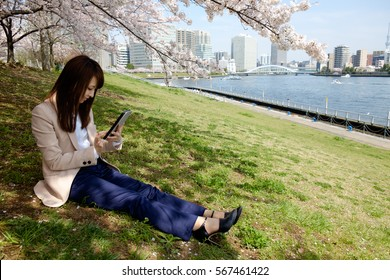 The woman who relax under the cherry tree