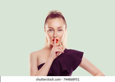 Woman wide eyed asking for silence or secrecy with finger on lips hush hand gesture light green background wall Pretty girl placing fingers on lips shhh sign symbol. Negative emotion facial expression