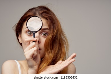 woman with wide open eyes holds magnifying glass in her hand