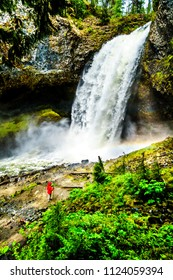 Woman in a Wind Breaker in the mist at the bottom  of Moul Falls in Grouse Creek in Wells Gray Provincial Park at Clearwater, British Columbia, Canada