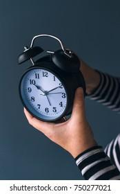 Woman winding retro alarm clock, concept of daylight saving time, selective focus