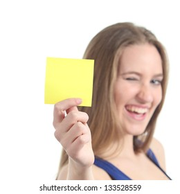 Woman winking and showing a blank yellow paper note isolated on a white background