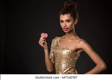 Woman winning - Young woman in a classy gold dress holding two red chips, a poker of aces card combination.