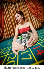 Woman wins roulette and takes away piles of chips at the casino