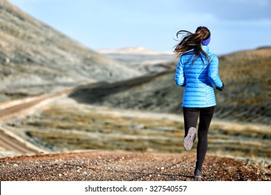 Woman winter and autumn running in down jacket. Female running jogging on mountain trail in beautiful landscape.