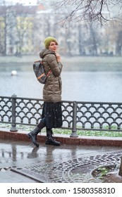 Woman in winter clothes catching snowflakes and smiling at Patriarch ponds in Moscow Russia