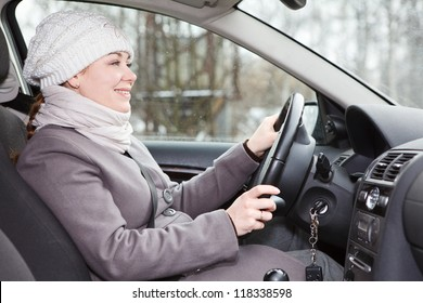 Woman in winter clothes driving a car looking forward