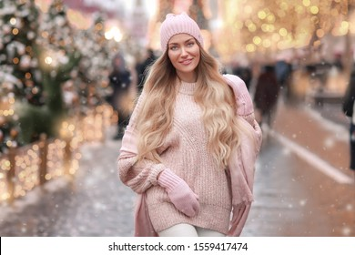 Woman in winter clothes in a pink sweater walks around the New Year decorated city.
