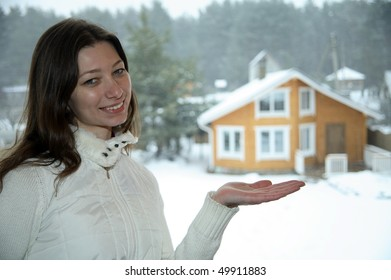 Woman in winter clothes showing new house