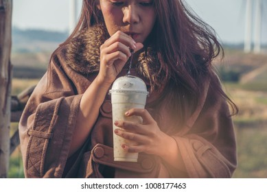 Woman in winter Overcoat  drinking sweet milk shake chocolate protein powder milkshake smoothie at park Drinking protein low fat milk nutrition diet after gym.Healthy life