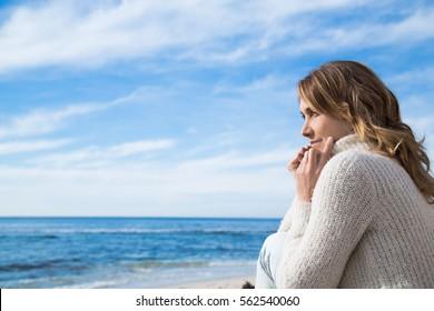 Frau im Winter am Meer mit Blick auf den Horizont