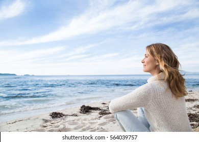 woman in winter sitting on the beach