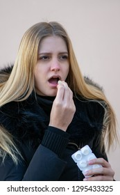 Woman in winter taking a pill