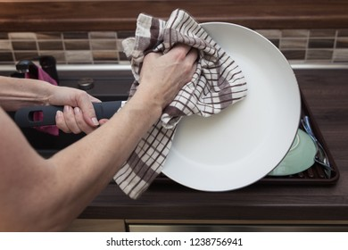 woman wipes dishes in the kitchen