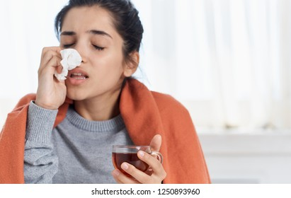 Woman wipes her nose with a napkin health problems