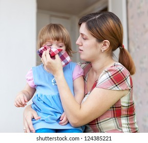woman wipes snivels her daughter at home