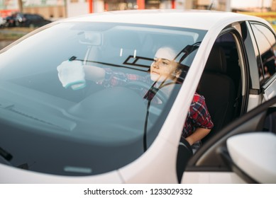 Woman wipes windshield of car from the inside