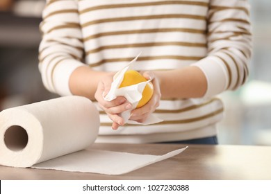 Woman wiping apple with paper towel in kitchen