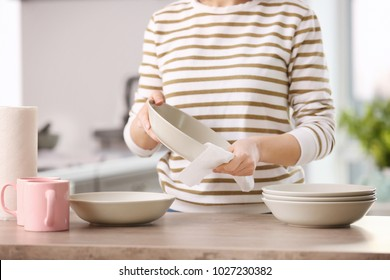 Woman wiping dishware with paper towel in kitchen