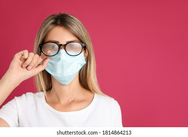 Woman wiping foggy glasses caused by wearing disposable mask on pink background, space for text. Protective measure during coronavirus pandemic - Shutterstock ID 1814864213