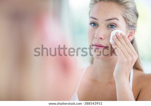 Женщина вытирая ее лицо с ватным тампоном в ванной комнате