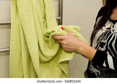Woman is wiping her hands using green towel in bathroom