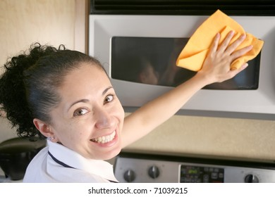 Woman wiping microwave with a rag looking back and smiling