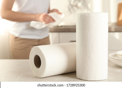 Woman wiping plate with towel in kitchen, focus on paper rolls