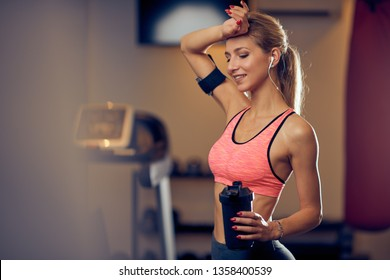 Woman wiping sweat and holding in other hand water while standing in gym. Healthy lifestyle concept.
