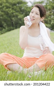 The woman wiping the sweat with a towel while sitting on the hill