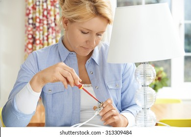 Woman Wiring Electrical Plug On Lamp At Home